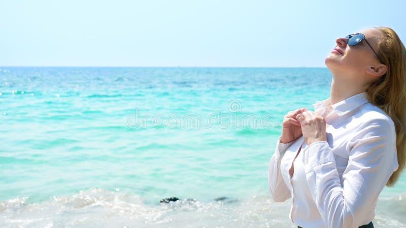 Mulher de negócio na praia aprecia a vista do mar Desabotoou sua camisa e respira no ar de mar fotografia de stock