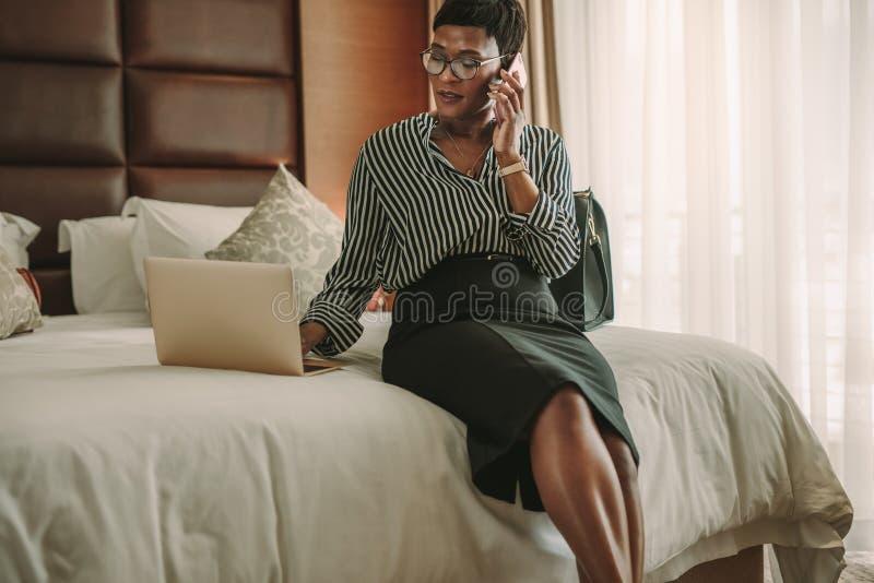 Mulher de negócio na sala de hotel usando o portátil e o smartphone imagem de stock royalty free