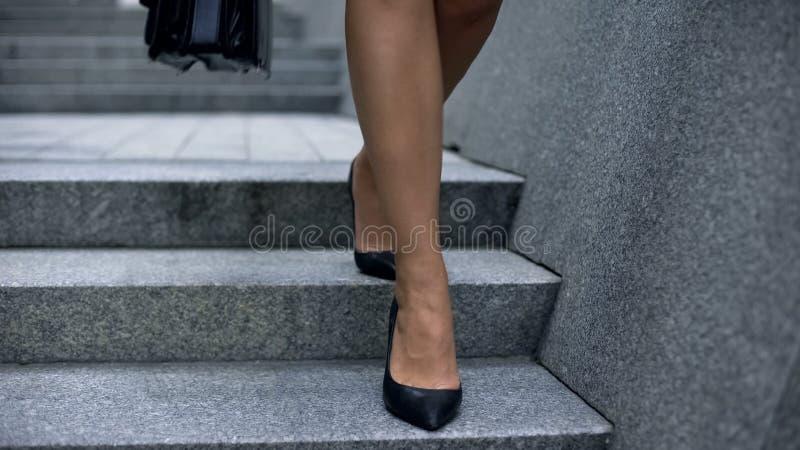 Mulher de negócio nos saltos altos que anda abaixo das escadas, pés cansados, veias varicosas imagem de stock royalty free