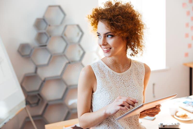 Mulher de negócio nova alegre que usa a tabuleta no escritório fotografia de stock