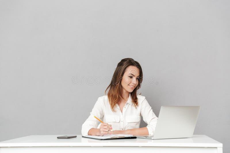 Mulher de negócio nova alegre surpreendente que usa notas da escrita do laptop fotos de stock royalty free