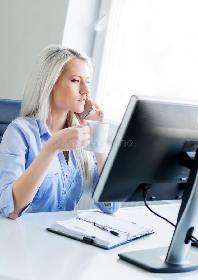 Mulher de negócio nova, atrativa e segura que trabalha no escritório fotos de stock