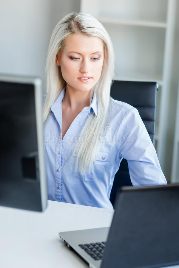 Mulher de negócio nova, atrativa e segura que trabalha no escritório imagens de stock