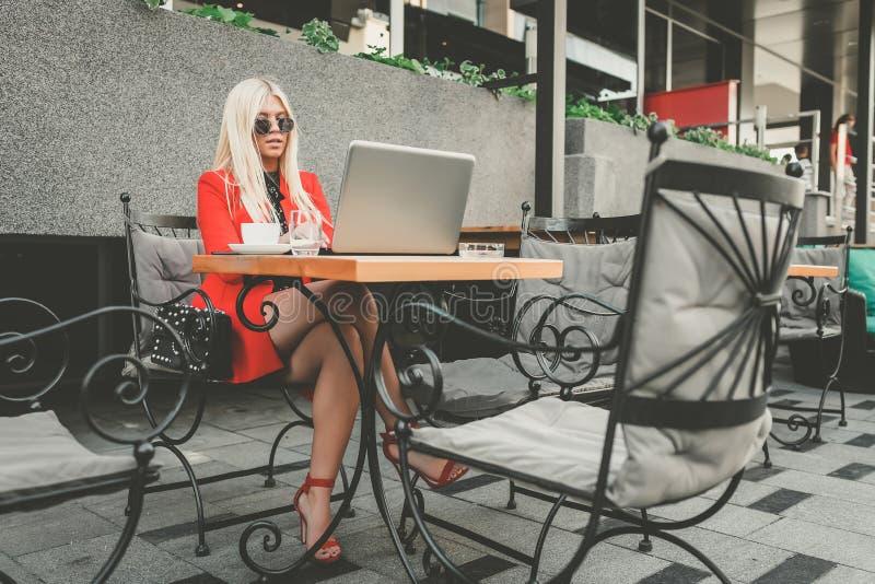 Mulher de negócio nova atrativa que trabalha no portátil no café exterior fotografia de stock royalty free