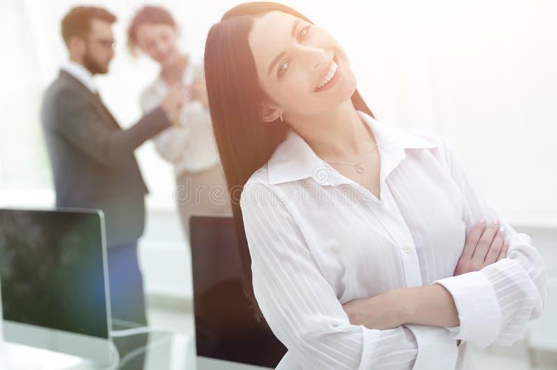 Mulher de negócio nova bem sucedida no fundo de um local de trabalho fotos de stock royalty free