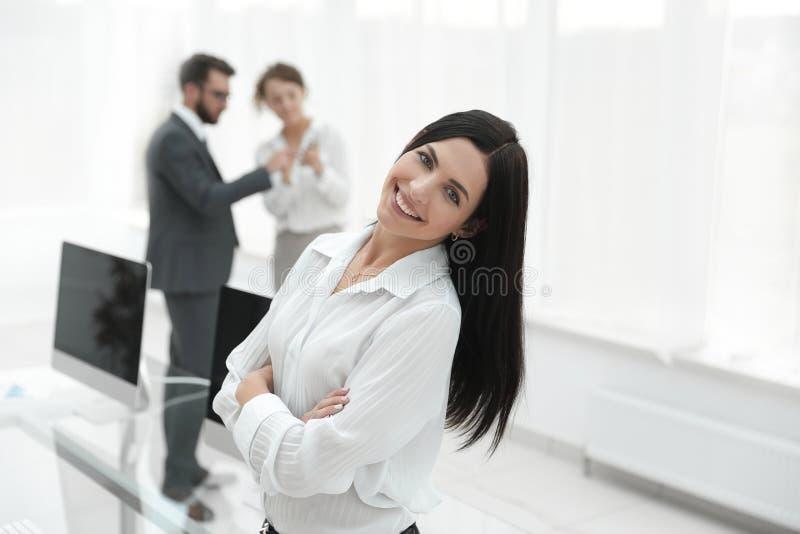 Mulher de negócio nova bem sucedida no fundo de um local de trabalho fotografia de stock