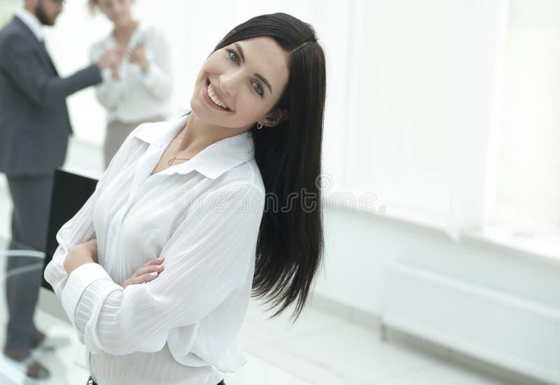 Mulher de negócio nova bem sucedida no fundo de um local de trabalho imagem de stock