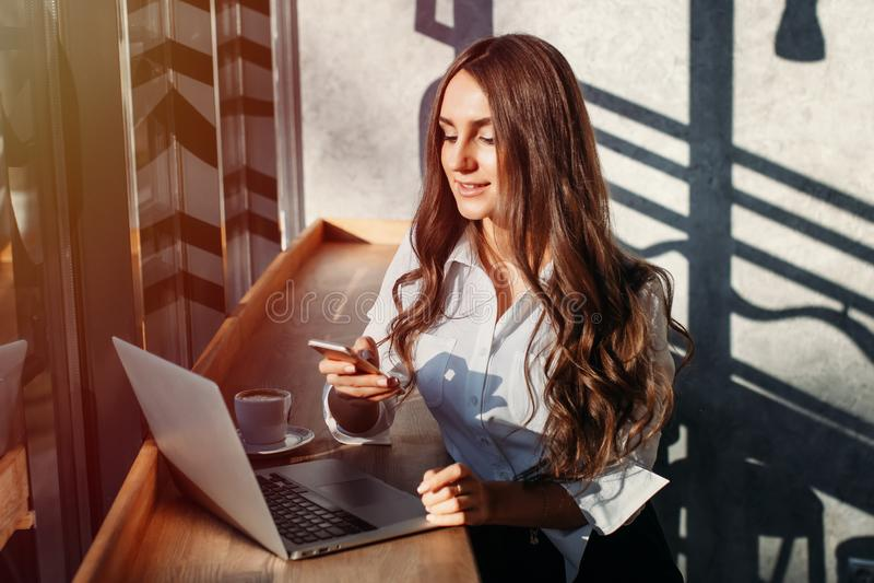 Mulher de negócio nova bonita na blusa branca usando o portátil e o smartphone, café das bebidas em uma tabela em um café fotos de stock
