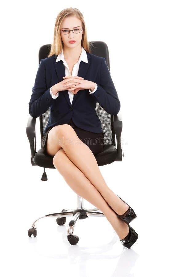 Mulher de negócio nova bonita que senta-se em uma cadeira. imagem de stock royalty free