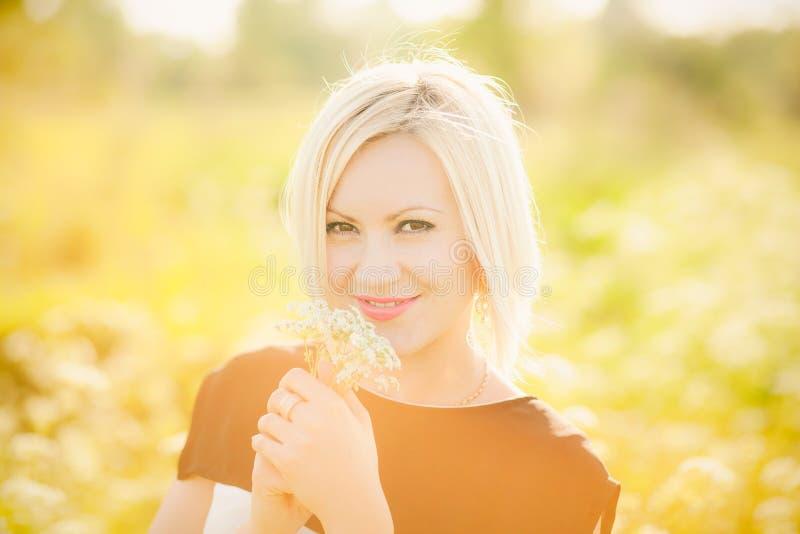 A mulher de negócio nova com campo floresce nas mãos fora em seguida fotografia de stock royalty free