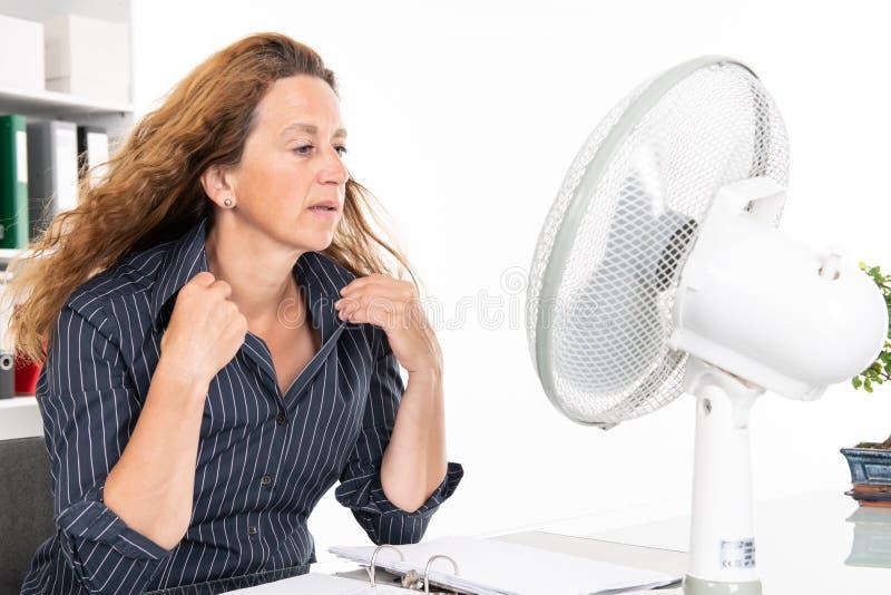 Mulher de negócio nova com o ventilador em sua mesa no summerly quente fotos de stock royalty free