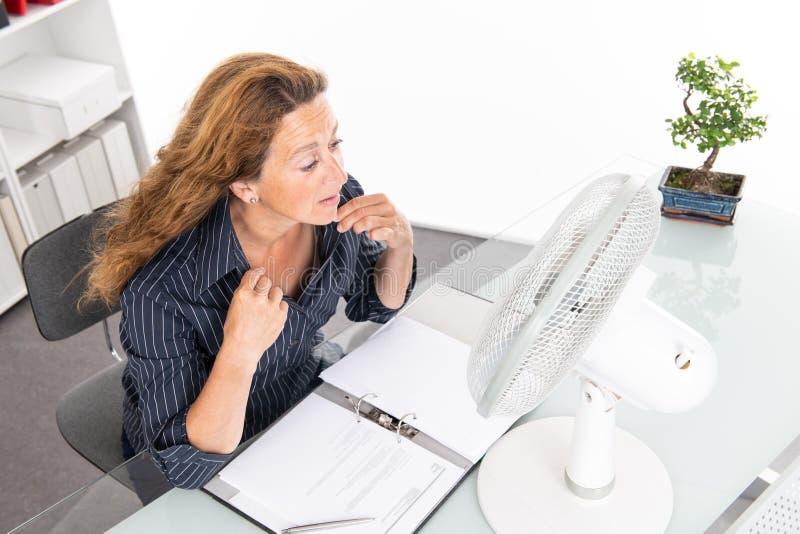 Mulher de negócio nova com o ventilador em sua mesa no summerly quente foto de stock royalty free