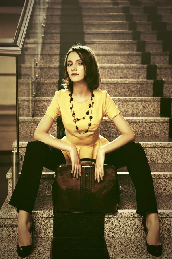 Mulher de negócio nova da forma com a bolsa que senta-se em etapas fotografia de stock royalty free
