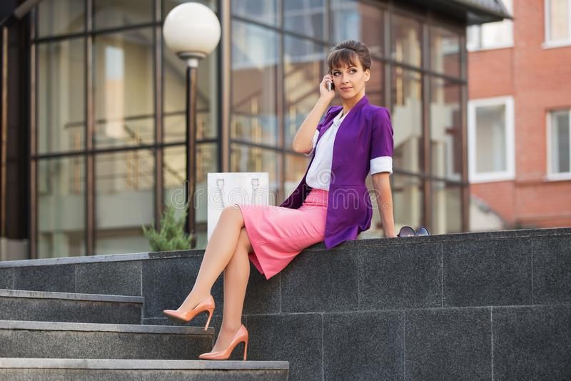 Mulher de negócio nova da forma no blazer roxo que chama o telefone celular fotos de stock