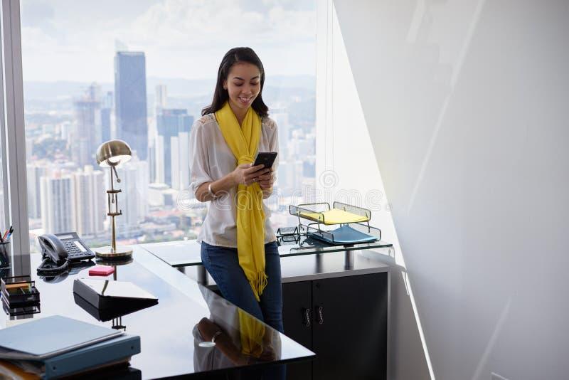 Mulher de negócio nova de Latina com o telefone no escritório 4 imagem de stock