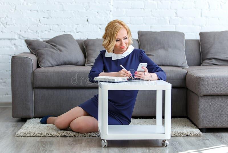 Mulher de negócio nova de sorriso que olha em na seu telefone e escrita imagens de stock
