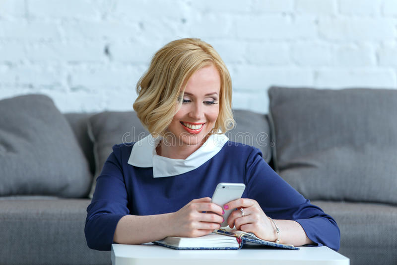 Mulher de negócio nova de sorriso que olha em seu telefone imagens de stock royalty free