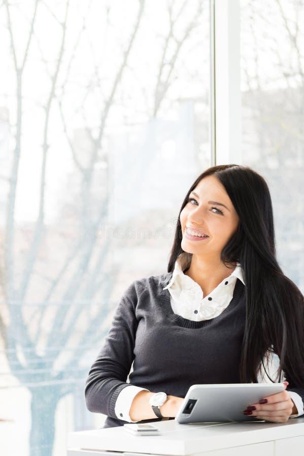 Mulher de negócio nova de sorriso que usa o PC da tabuleta ao estar a janela próxima relaxado em seu escritório imagem de stock