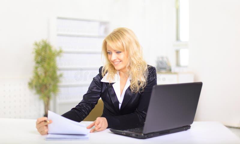 Mulher de negócio nova de sorriso que usa o portátil no trabalho fotografia de stock