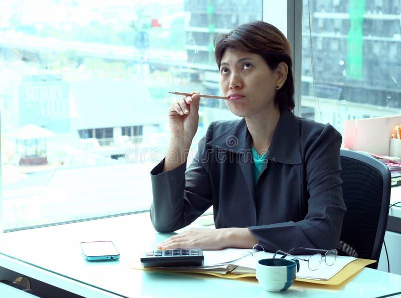 Mulher de negócio nova do retrato incorporado que trabalha na mesa de escritório imagem de stock