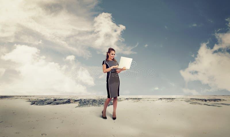 Mulher de negócio nova em um deserto usando um laptop fotografia de stock