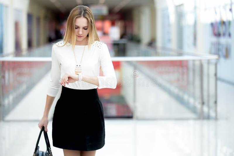 Mulher de negócio nova em uma precipitação, olhando para o tempo no relógio de pulso fotografia de stock