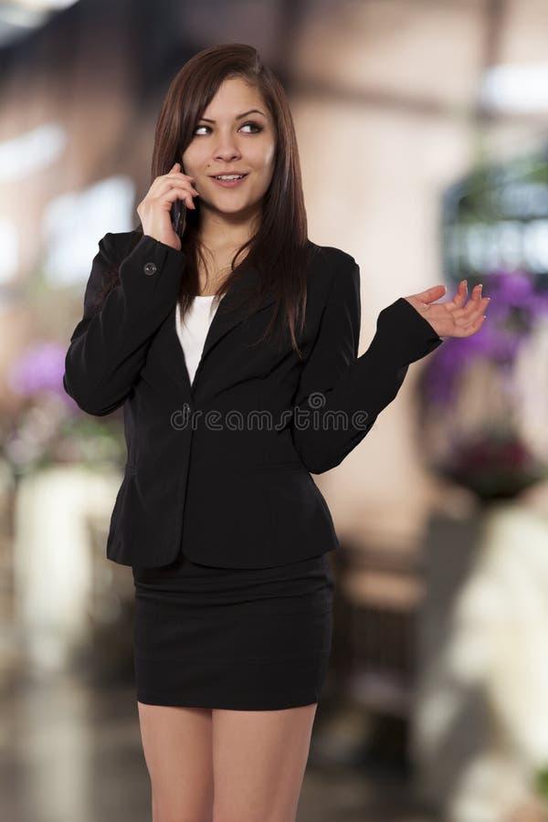 A mulher de negócio nova fala em seu telemóvel. imagens de stock