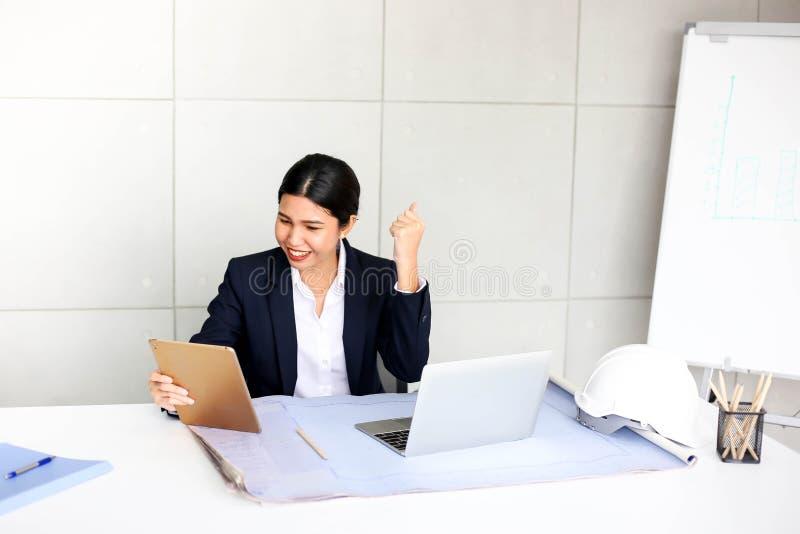 Mulher de negócio nova feliz bonita que trabalha no escritório fotografia de stock