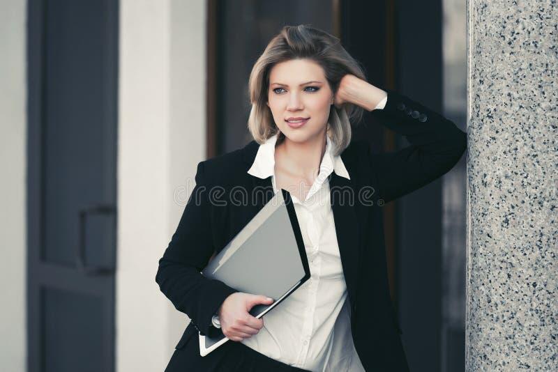 Mulher de negócio nova feliz com a pasta de arquivos no prédio de escritórios fotos de stock