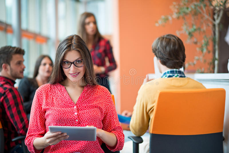 Mulher de negócio nova feliz com seu pessoal, grupo dos povos no fundo no escritório brilhante moderno dentro fotos de stock royalty free
