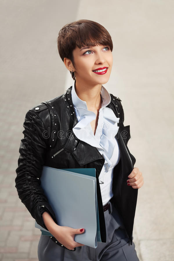 Mulher de negócio nova feliz da forma no casaco de cabedal com dobradores foto de stock