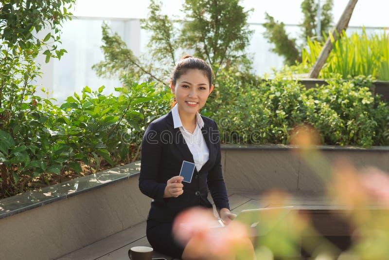 Mulher de negócio nova feliz do retrato que guarda o cartão de crédito e o lapt imagem de stock royalty free