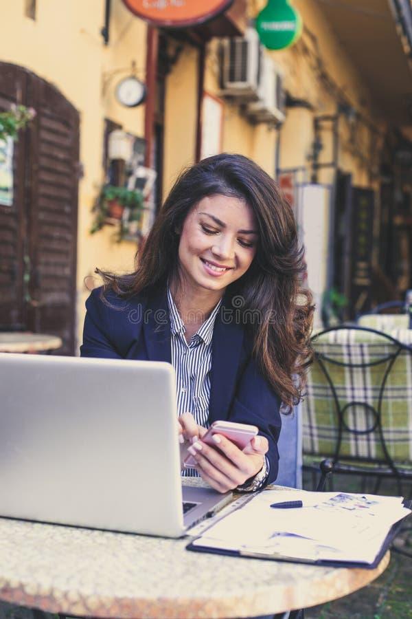 Mulher de negócio nova feliz que trabalha no café, usando o telefone celular fotografia de stock royalty free