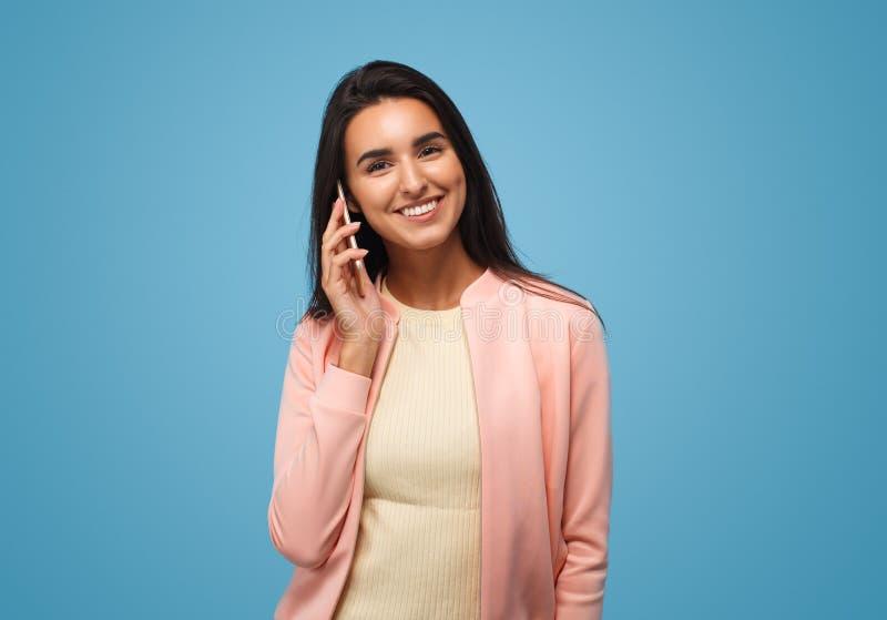 Mulher de negócio nova latino-americano que guarda o smartphone fotos de stock royalty free