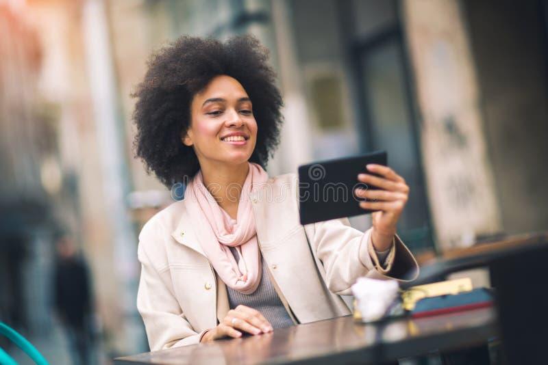 mulher de negócio nova Misturado-competida que usa a tabuleta digital fotografia de stock