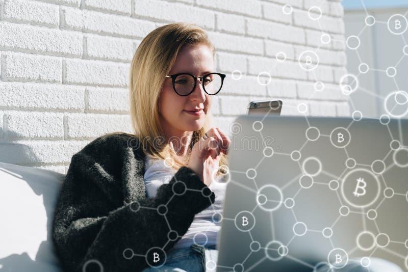 A mulher de negócio nova nos vidros senta-se no portátil e usa-se o smartphone No infographics do primeiro plano, ícones do bitco foto de stock royalty free