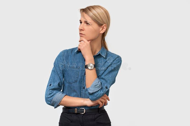 Mulher de negócio nova pensativa desconfiado na camisa da sarja de Nimes com o dedo que toca em seu queixo e que olha ao um lado  imagens de stock