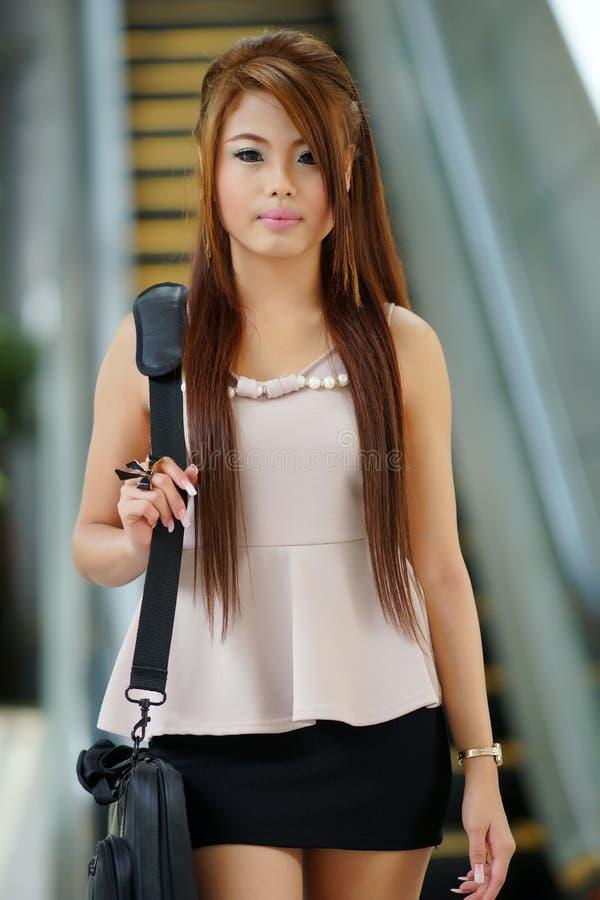 Mulher de negócio nova que anda na frente da escada rolante imagens de stock royalty free