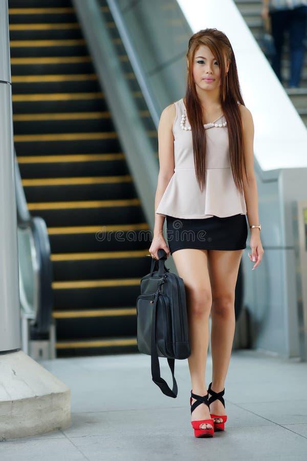 Mulher de negócio nova que anda na frente da escada rolante fotos de stock