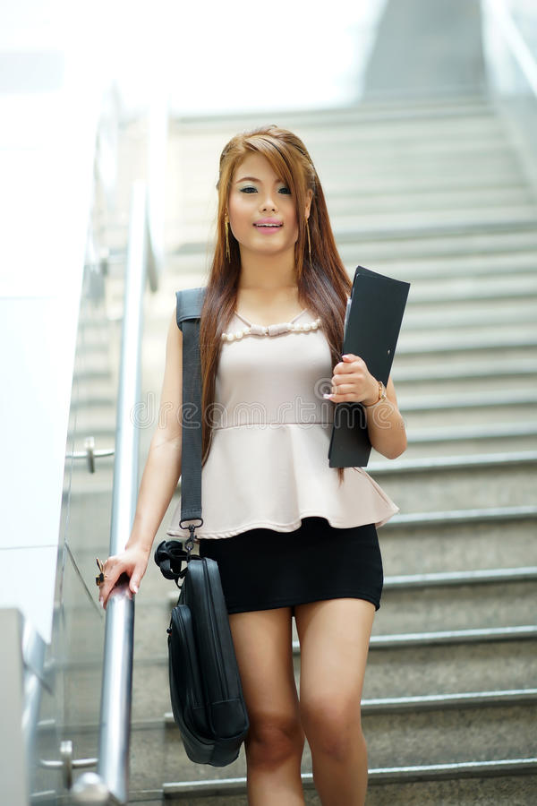 Mulher de negócio nova que anda na frente da escada rolante foto de stock royalty free