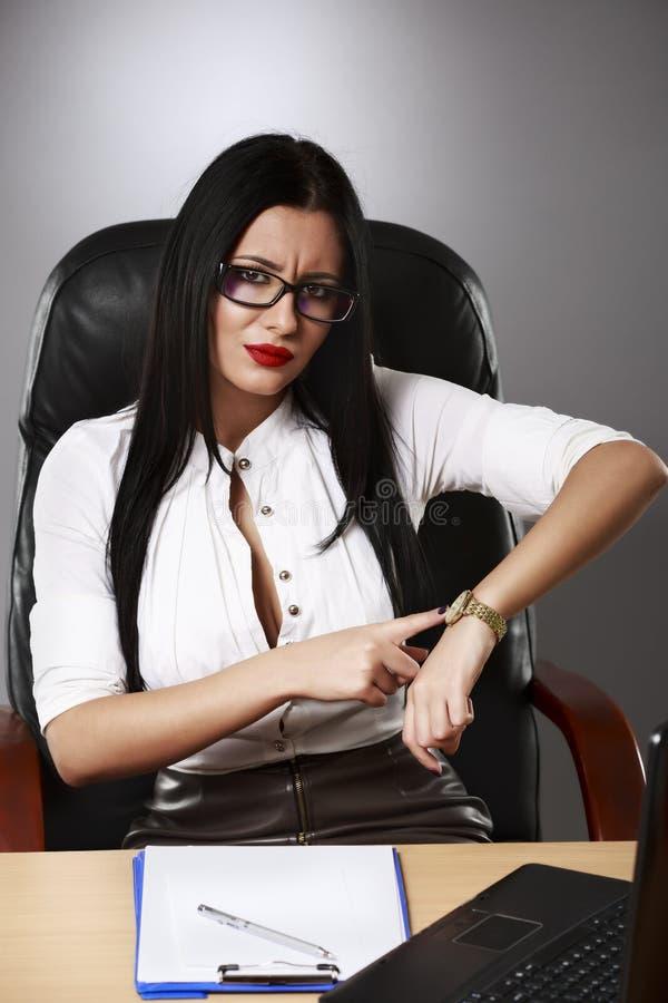 Mulher de negócio nova que aponta um dedo no pulso de disparo era tempo fotografia de stock royalty free