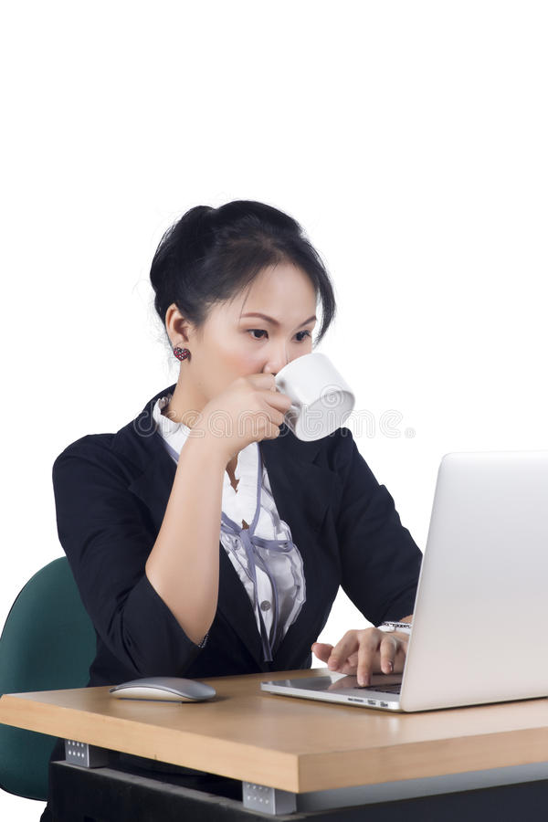 Mulher de negócio nova que boceja em sua mesa com uma chávena de café fotos de stock