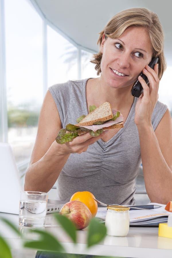 Mulher de negócio nova que come a salada em um grande escritório das janelas, tendo o almoço saudável no local de trabalho ao usa imagens de stock