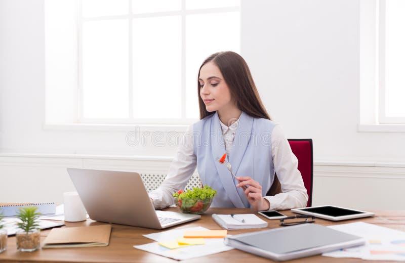 Mulher de negócio nova que come a salada no escritório foto de stock