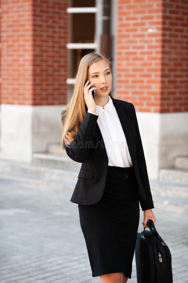 Mulher de negócio nova que deixa seu trabalho com a bolsa em sua mão t imagem de stock