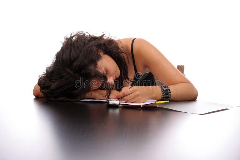 Mulher de negócio nova que dorme na mesa fotografia de stock royalty free