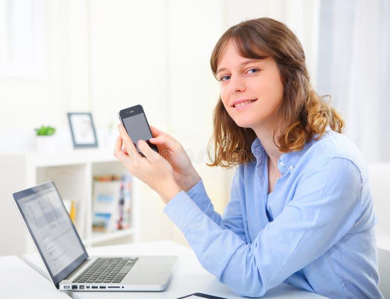 Mulher de negócio nova que escreve um texto em seu móbil imagens de stock