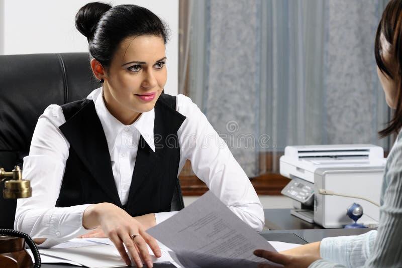 Mulher de negócio nova que escuta fotografia de stock
