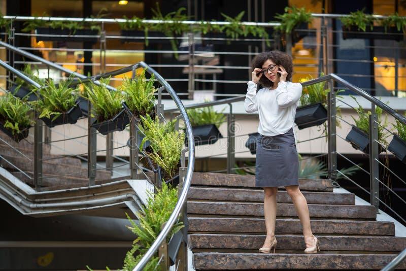 Mulher de negócio nova que fala na posição móvel no vão das escadas foto de stock royalty free