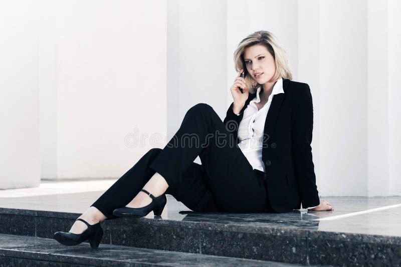 Mulher de negócio nova que fala no telefone celular no prédio de escritórios imagens de stock royalty free